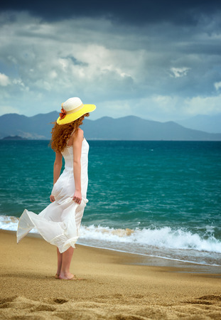Lonely woman in a white dress standing at the sea shore and watching the storm  Artistic colors added photo