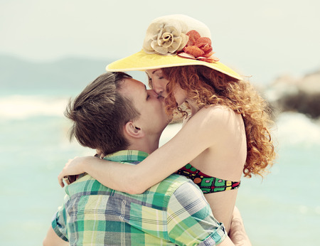 beach kiss: Beautiful redhead pretty  girl kissing handsome boy  Stock Photo