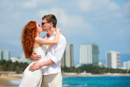 trang: Attractive boy and girl posing and kissing on a beach  Stock Photo