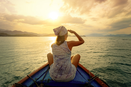 traveller: Woman traveling by boat at sunset among the islands  Stock Photo