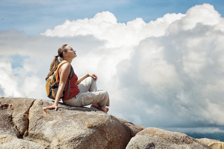 Young woman sitting on a rock with backpack and looking to the clouds