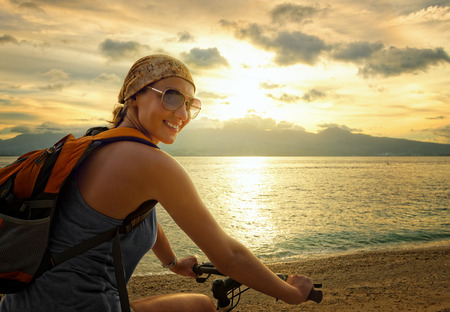 Young woman with backpack standing on the shore near his bike and smiling