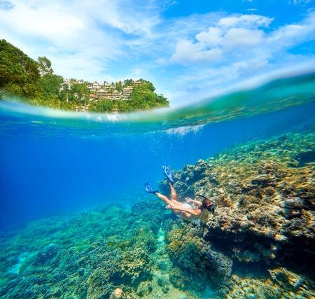 Travel card se žena, plovoucí na pozadí zelených ostrůvků a korálovým útesem v popředí