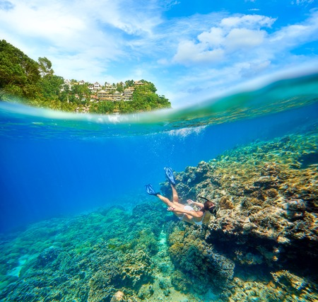 boracay: Travel card with a woman floating on a background of green islands and coral reef in the foreground