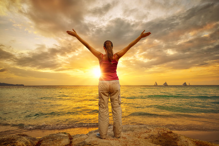 """standing water: Young woman with raised hands standing on shore and looking to a horizon  Photo â""""–18 in a series Adventure Travel"""