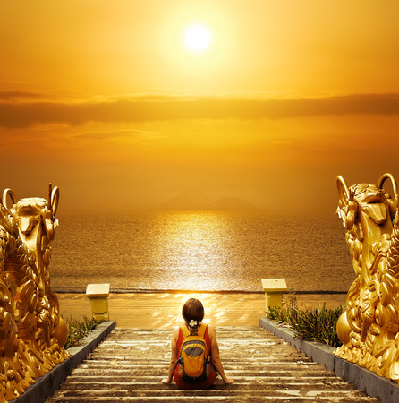 Hiker with backpack relaxing on the steps and enjoying sunset  Travel to Asia, happiness emotion, summer holiday concept Banco de Imagens