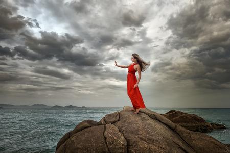 Mujer en el vestido rojo se encuentra en una colina con una hermosa vista al mar y las nubes dramáticas