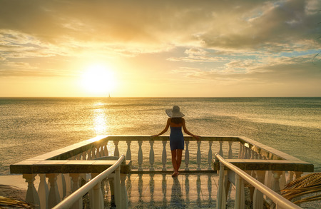 balcony view: Woman on balcony looking at the beautiful sunset Stock Photo
