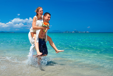 Happy young loving couple bride and groom, on wedding day on tropical sand beach photo