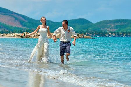 destination wedding: Happy Bride and groom running on a beautiful tropical sand beach.