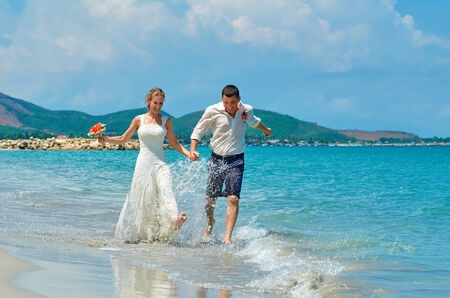 Happy Bride and groom running on a beautiful tropical sand beach. photo
