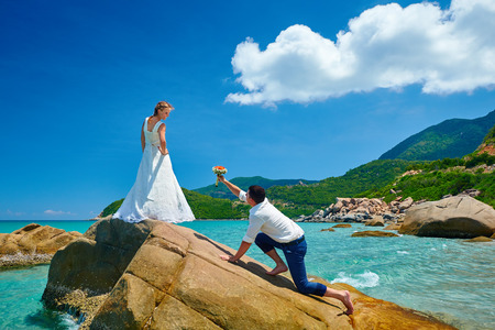 proposal of marriage: Loving couple on sea beach - a man making proposal with bouquet to his pretty woman in wedding dress