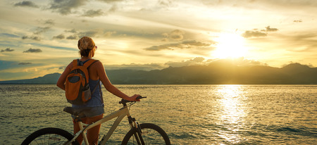 Young woman with backpack standing on the shore near his bike and enjoying the sunset over the sea on the background of the island Negros, Philippines.