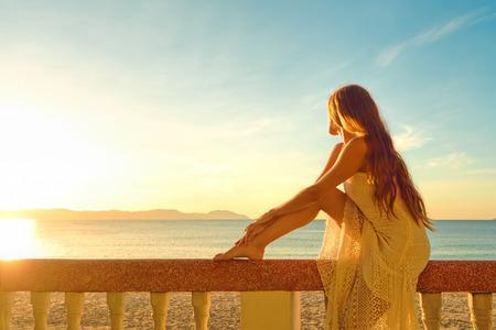 Žena na balkon pohledu na krásný západ slunce Reklamní fotografie