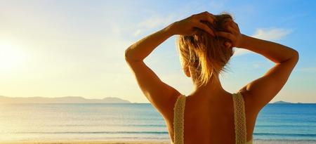 Zadní boční pohled na krásné mladé ženy, sledování na moři a zvedla ruce na sunrise.Panoramic pohledu