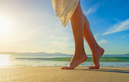 beach feet: Young woman in white dress walking alone on the beach in the sunrise.Closeup detail of female feet and golden sand on beach. Stock Photo