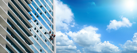 window repair: Group of workers cleaning windows on high rise building.Panoramic view