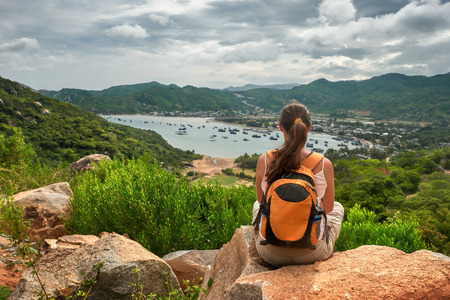 travel destination: Woman traveler looks at the edge of the cliff on the  sea bay of mountains in the background