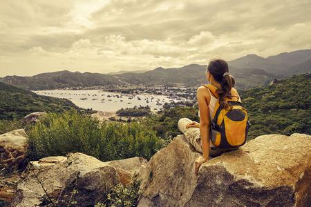 Žena cestovatel se dívá na okraji útesu na mořský záliv hor