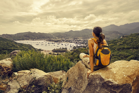 sits: Woman traveler looks at the edge of the cliff on the  sea bay of mountains