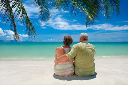 Happy senior caucasian couple sitting near the sea  and hugging.  Rear view. Foto de archivo