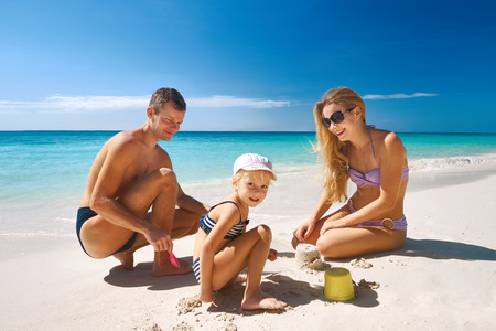 summer holiday bikini: Happy smiling family of playing with sand at beach in sunny day Stock Photo