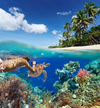 Mladá žena šnorchlování nad korálovém útesu v tropickém moři na pozadí zeleného ostrova
