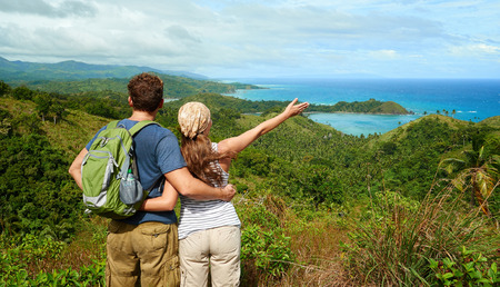 valley view: Hiker with backpack standing on top of the mountain with raised hands and enjoying valley view Stock Photo
