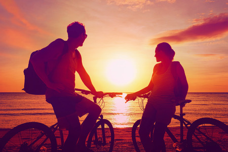 summer: Couple tourists with Bicycles Watching Sunset. Summer Nature Background with Beautiful Sky and Sea. Active Leisure Concept. Stock Photo