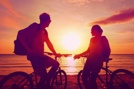 silueta ciclista: Turistas de par con las bicicletas mira puesta del sol. Fondo de verano de la naturaleza con hermoso cielo y el mar. Concepto de ocio activo.