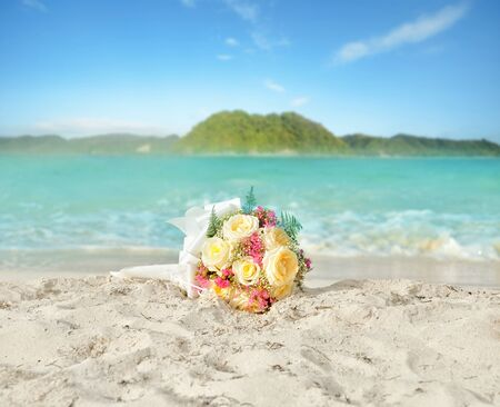 Wedding bouquet of roses on the shore of a tropical beach.