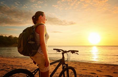 andando en bicicleta: Mujer joven con mochila de pie en la orilla cerca de su bicicleta y mirando la puesta de sol. Viajando a lo largo de Asia, estilo de vida activo concepto