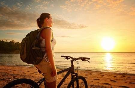 Young woman with backpack standing on the shore near his bike and looking on sunset. Traveling along Asia, active lifestyle concept