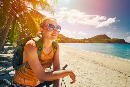 Young woman with backpack standing on the shore near his bike and looking on sea. Traveling along Asia, active lifestyle concept