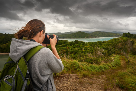 clouds making: Travelling woman photographer with backpack  making an inspiring landscape of dramatic clouds. Tourist girl traveling along Asia, active lifestyle concept Stock Photo
