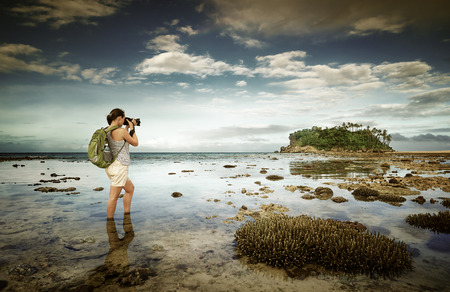 standing in the sea water traveler woman with backpack taking a landscape of amazing far island on the horizon.Traveling along Asia, active lifestyle concept Banco de Imagens