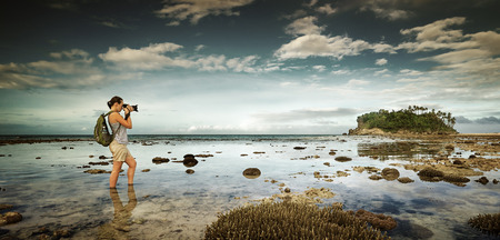 standing in the water traveler woman with backpack taking a landscape of nearby amazing island. Traveling along Asia, active lifestyle concept Archivio Fotografico