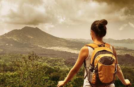discovering: Young backpacker traveling along mountains, happy female walking in the island to Bali, discovering world, summer vacation concept