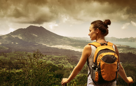 discovering: Young woman  backpacker traveling along mountains, happy female walking in the island to Bali, discovering world, summer vacation concept