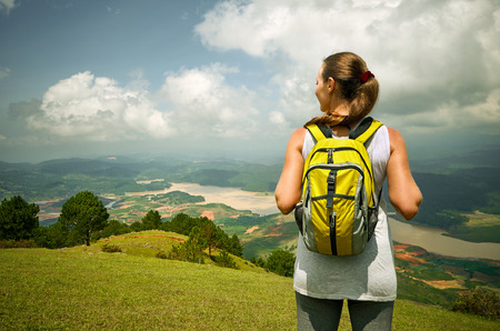 Portrait of happy traveler woman with backpack standing on top of the mountain and enjoying valley view photo