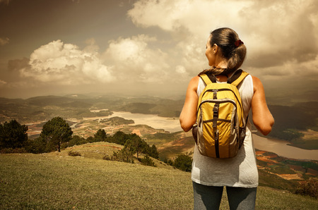 Portrait of happy traveler girl with backpack standing on top of the mountain and enjoying valley view photo