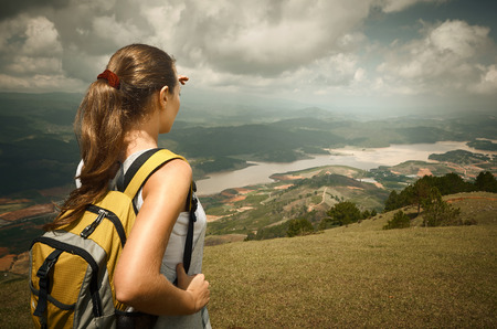 Woman hiker with backpack standing on top of the mountain and enjoying valley view photo