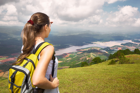 Young woman hiker with backpack standing on top of the mountain and enjoying valley view photo