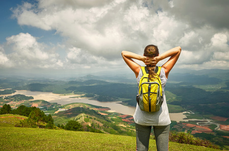 Portrait of happy traveler woman with backpack standing on top of the mountain and enjoying valley view with raised hands. Travel to Asia, happiness emotion, summer holiday concept photo