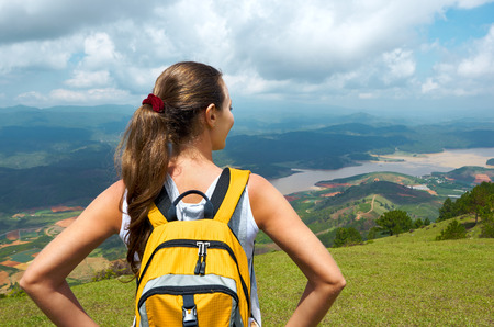 Portrait young woman hiker with backpack standing on top of the mountain and enjoying great valley view. Travel to Asia, happiness emotion, summer holiday concept photo
