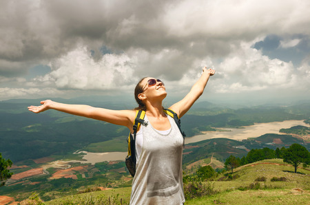 Portrait of happy traveler girl with raised up hands enjoying valley view, mountains landscape, travel to Asia, happiness emotion, summer holiday concept Foto de archivo