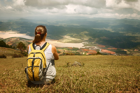 Young tourist with backpack relaxing on top of the mountain and enjoying beatiful landscape view.