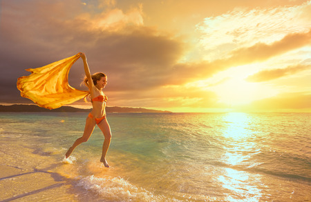 Happy carefree woman running in the sunset on the beach. Vacation vitality healthy living concept