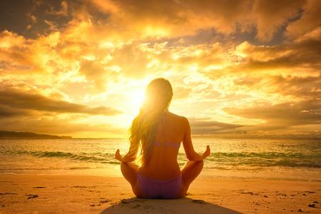 Mladá žena cvičí jógu na pláži při západu slunce. Reklamní fotografie