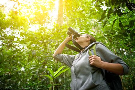 Turistická hledá dalekohledem se domnívá, volně žijících ptáků v jungle.Bird sledovali zájezdy